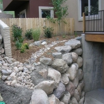 Elevated mini garden at Durango Townhome above large boulder retaining wall by Gardenhart Landscape & Design