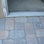 Landscape pavers fit perfectly under threshold when grade is correctly anticipated by Gardenhart Landscape & Design
