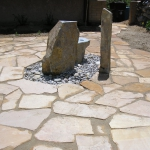 Pre-fab rock water fountain with circular flagstone patio with herb and edible garden area by Gardenhart Landscape & Design