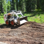 Landscape Designer uses a skid steer to rough grade a backyard to get ready for planting in Durango Colorado.